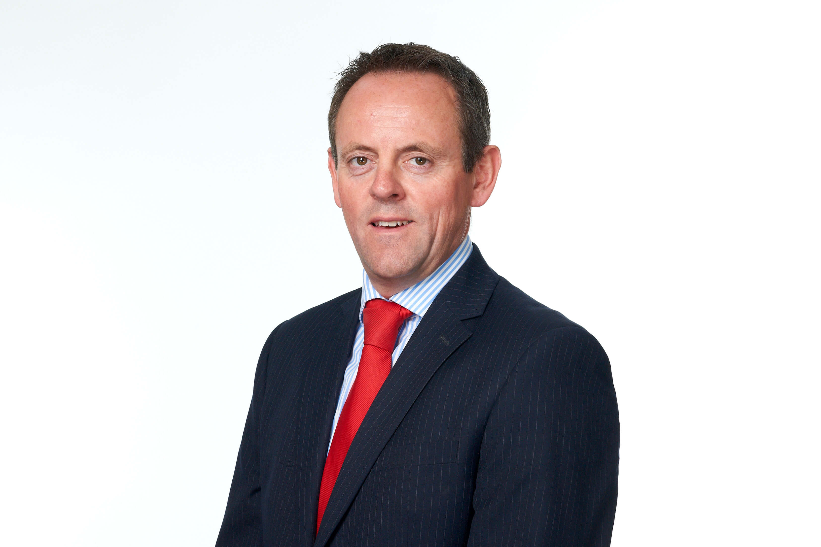 Simon Wilson, Serious Injury Solicitor, in a black suit with a red tie