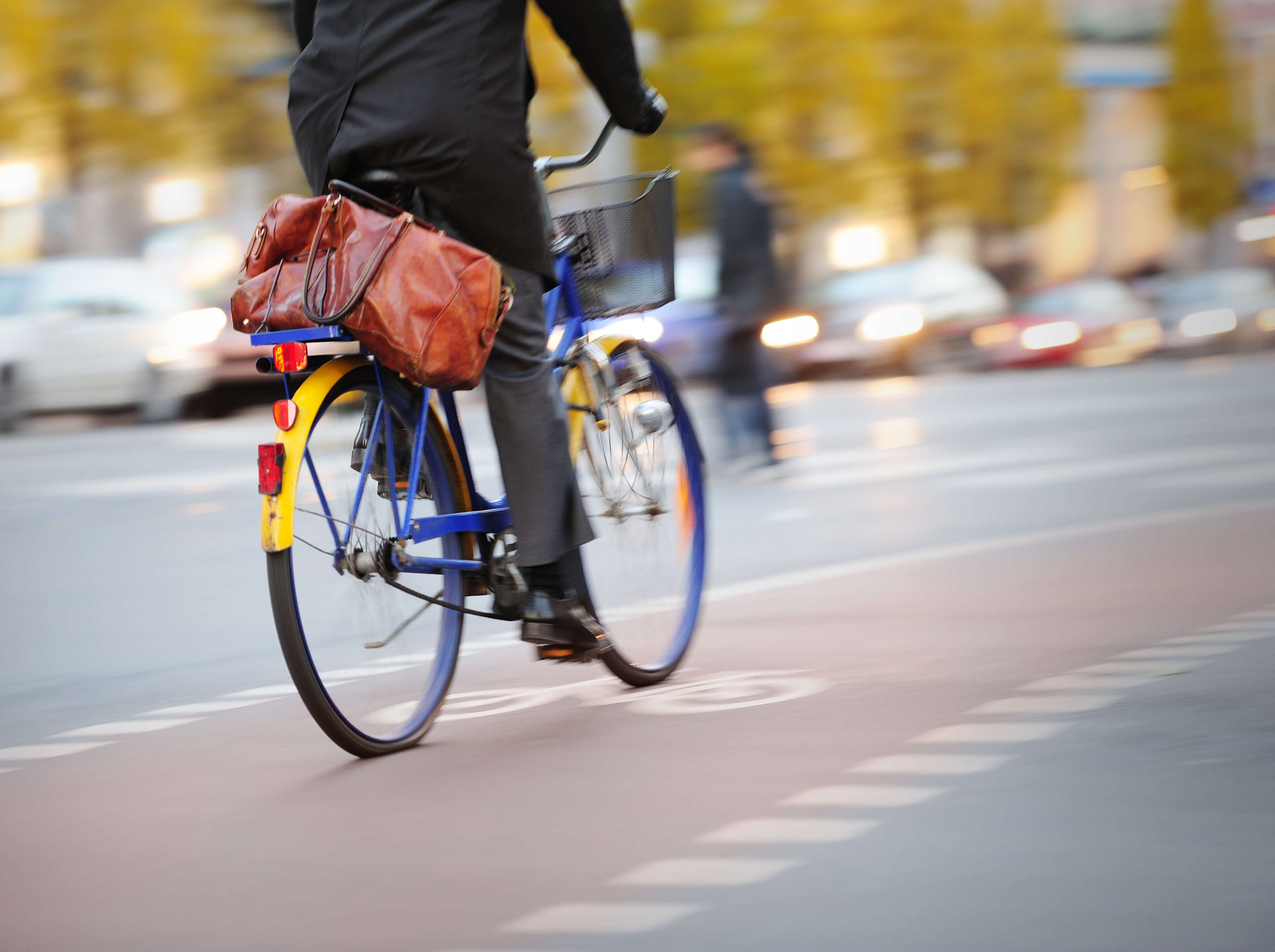 A man rides a blue and yellow bicycle along a busy road