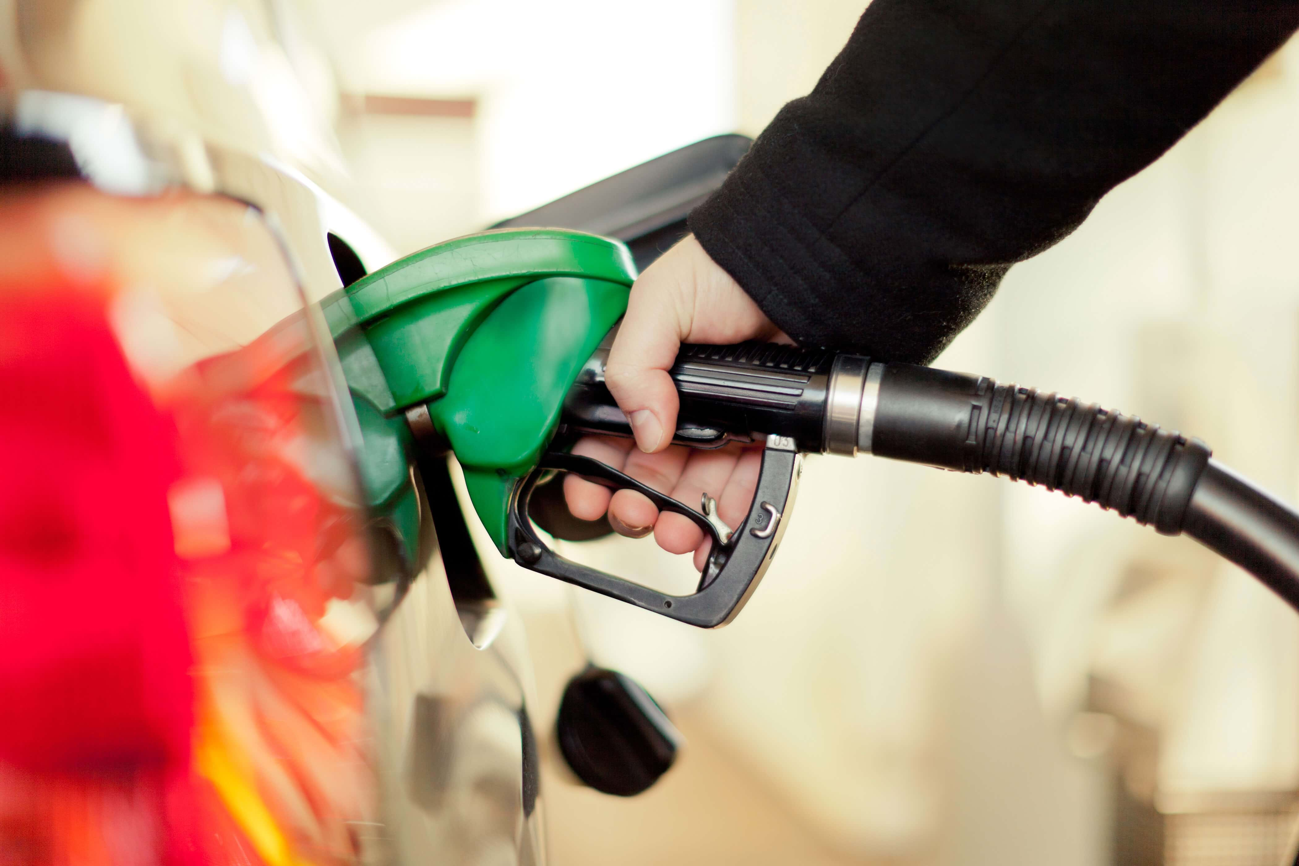 A driver fills up their car with petrol at a petrol station