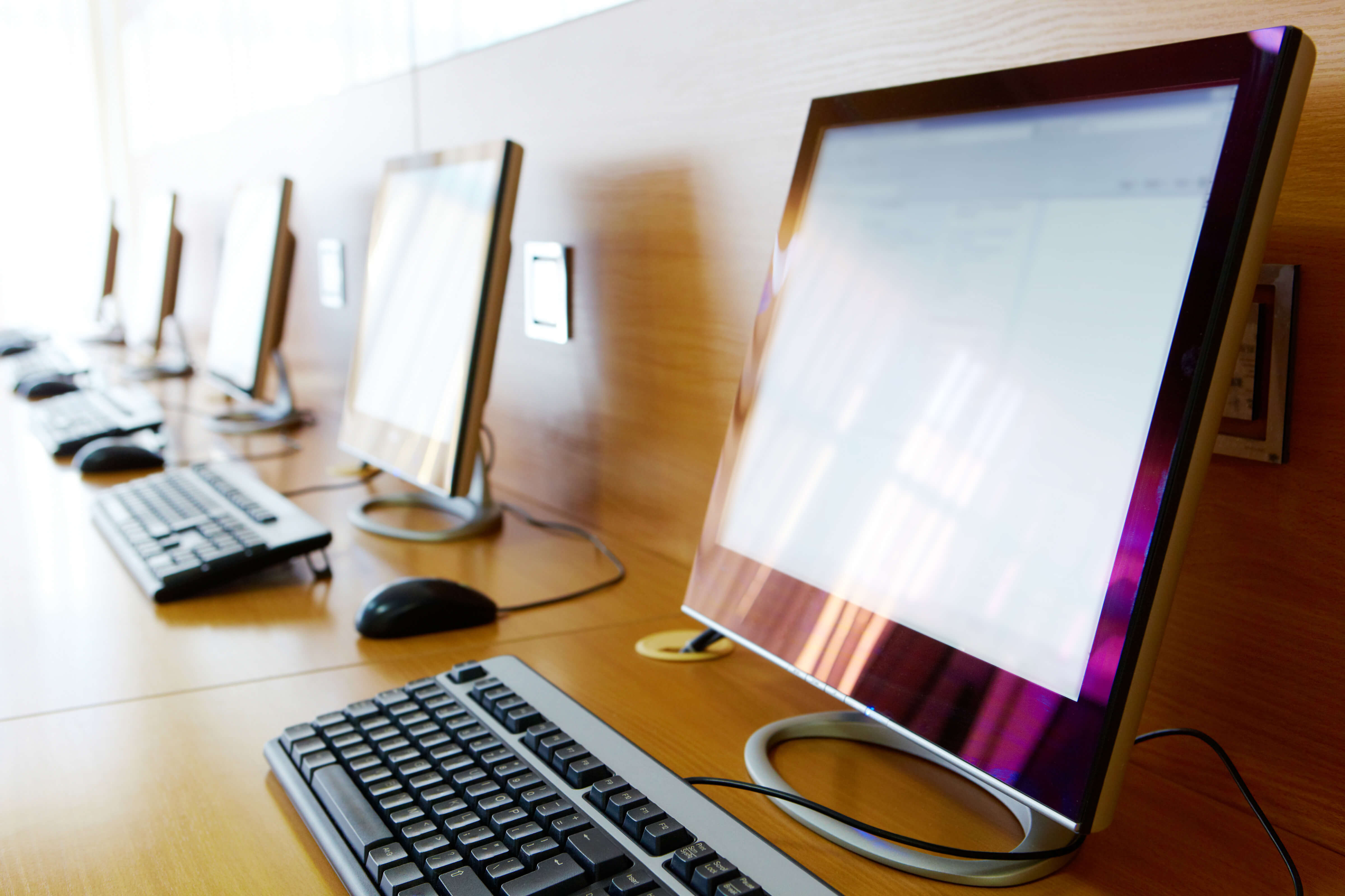 A row of desktop computers used by students
