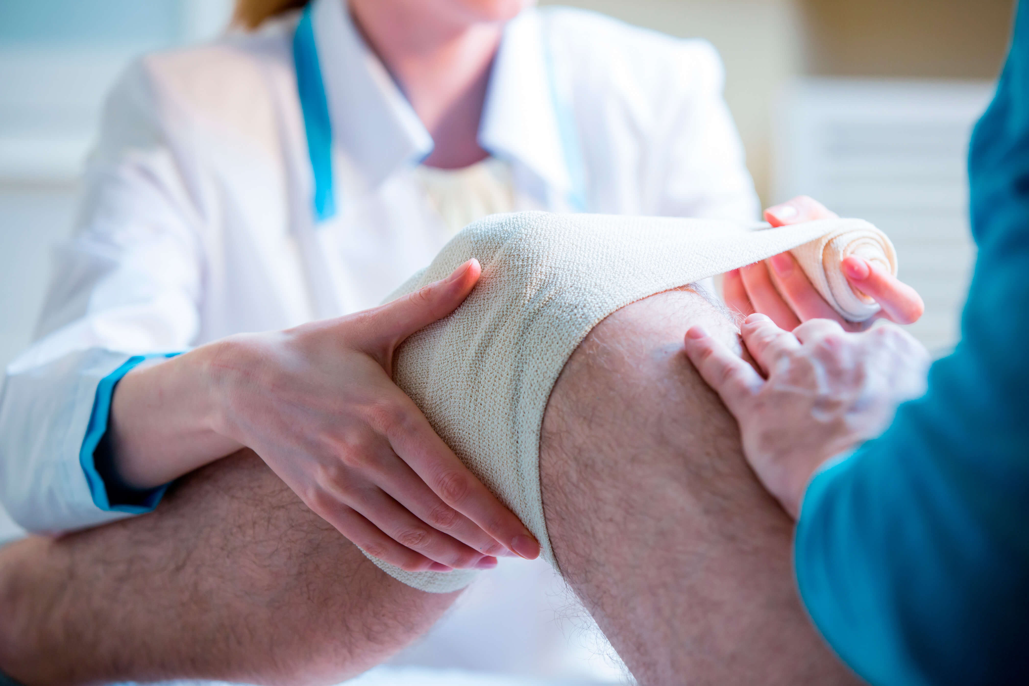 A man has his knee bandaged up by a nurse after an accident at work