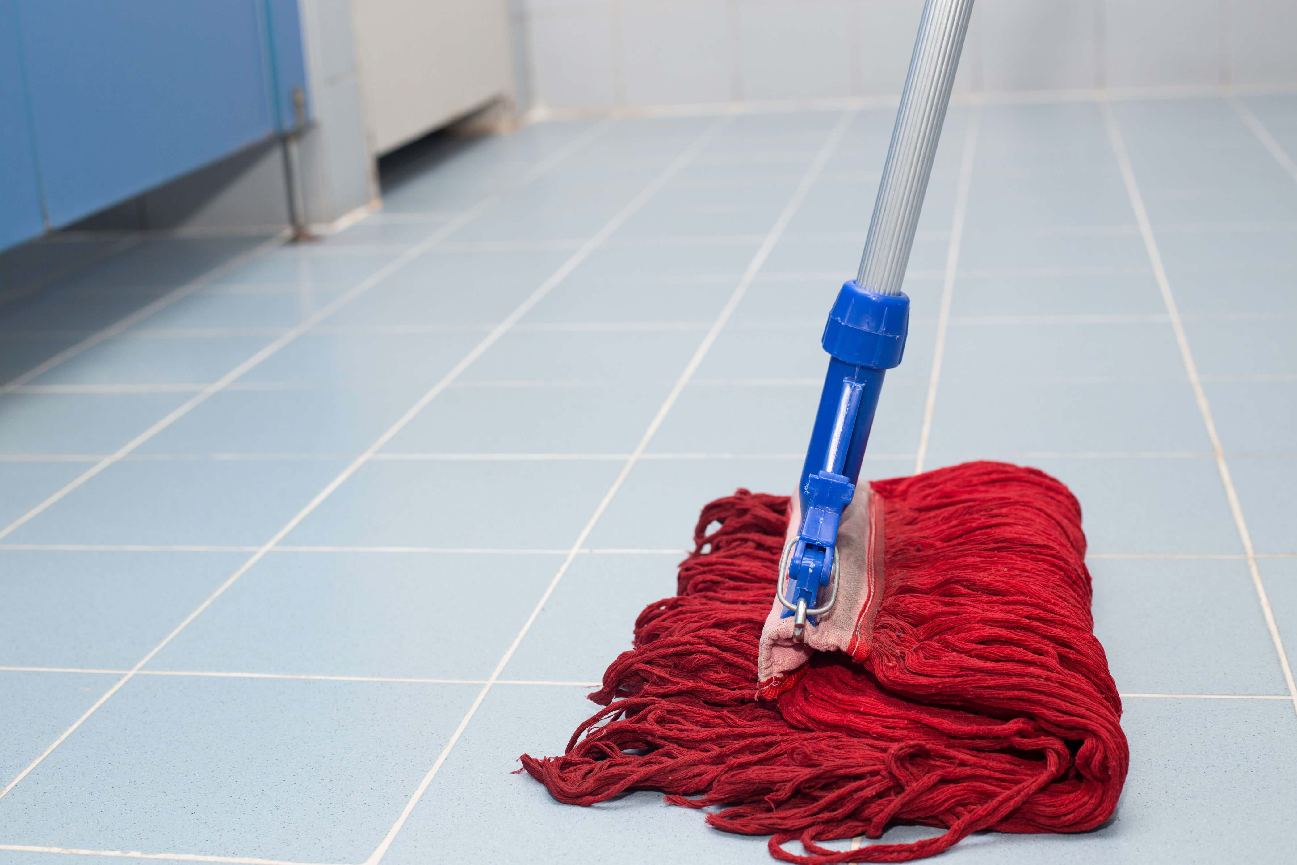 A mop wipes the floor of a rest room, which caused an accident at work