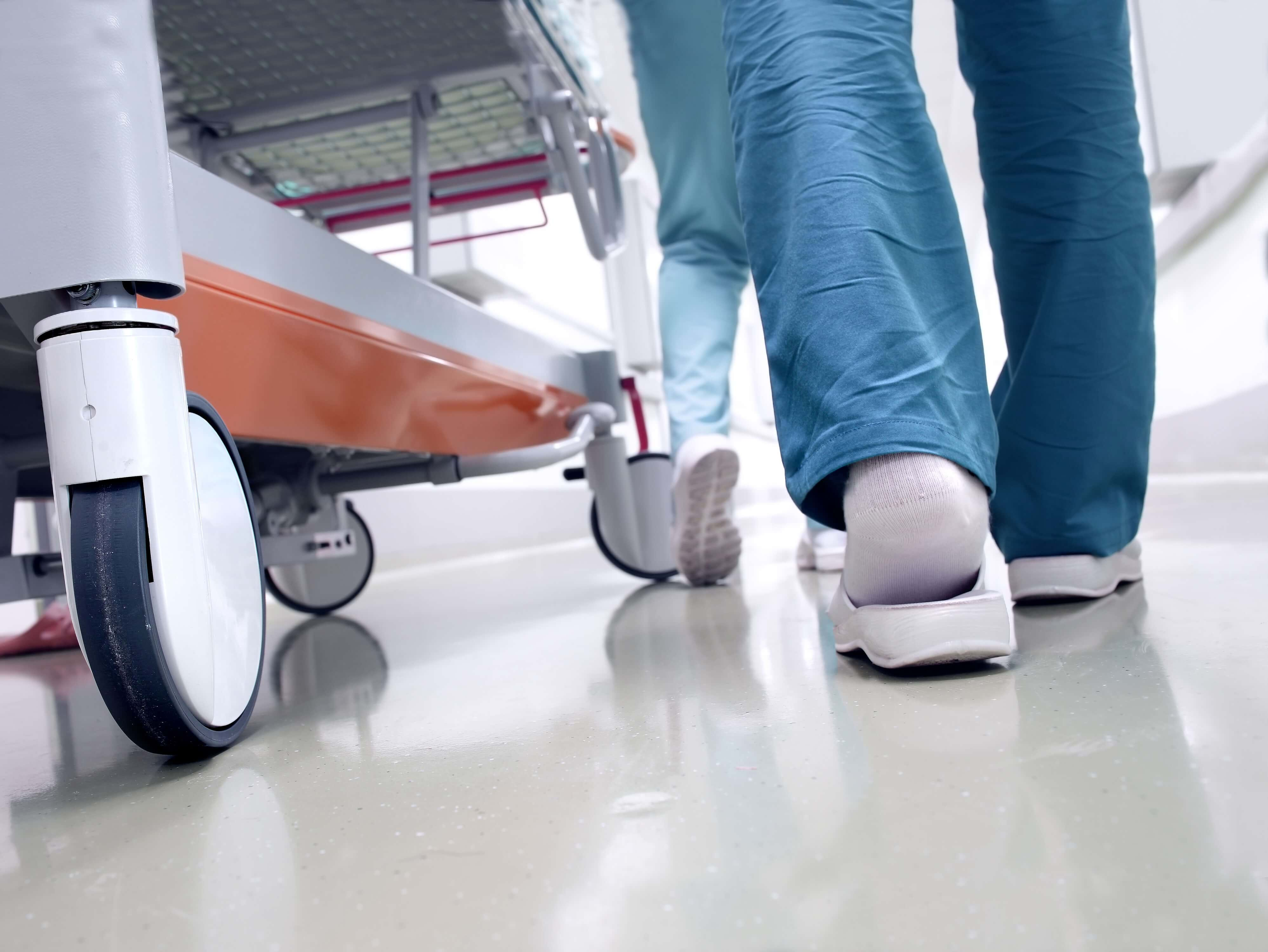 A patient trolley being pushed by a member of staff through a hospital