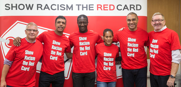 A team of people at Thompsons Solicitors law firm with celebrities wearing 'Show Racism the Red Card' red T-shirts.