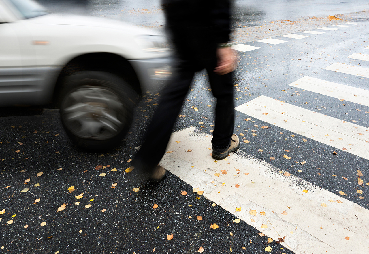 A man walks across a zebra crossing on the road while a white car comes towards him around the corner