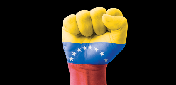 A fist painted in yellow, blue and red with stars, raised for the Venezuela solidarity campaign.
