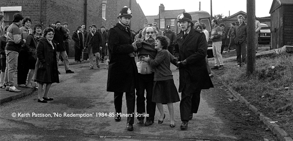 Two police officers haul a man through the street during the miners strike in 1984