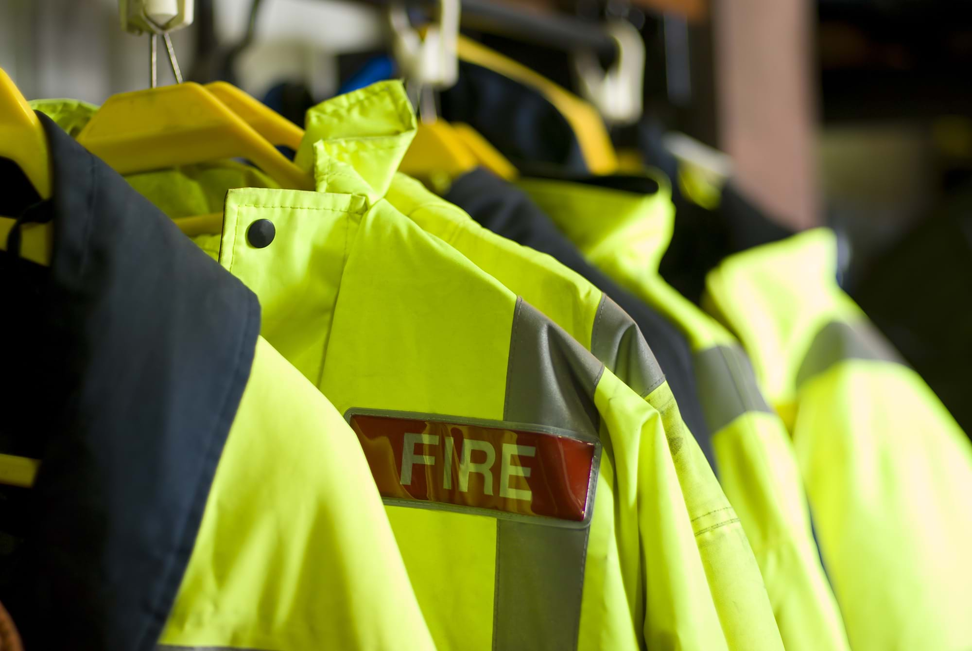 A row of Firefighter uniforms hanging from coathangers