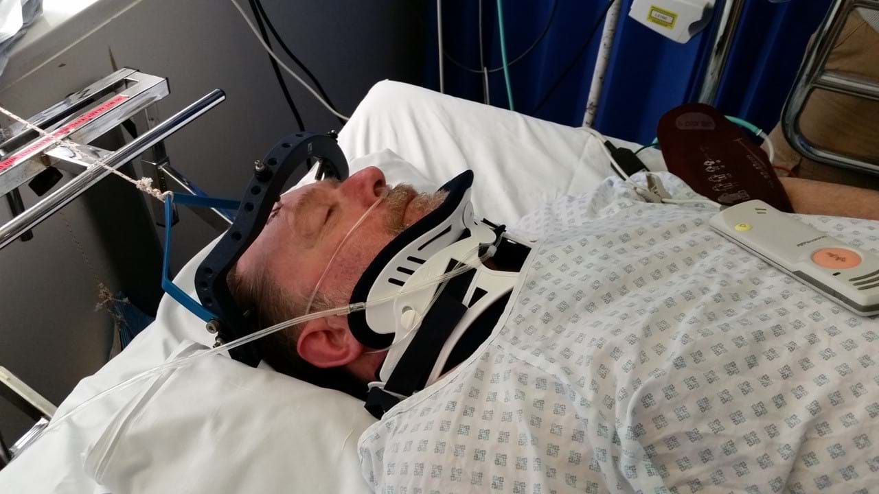 Injured man lying down in hospital bed